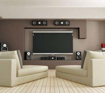 Ein Wohnzimmer mit einem großen Fernseher und vielen Lautsprechern