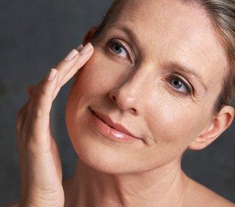 Frau circa Mitte 40 cremt sich das Gesicht ein