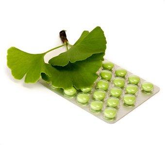 Gingkoblätter liegen auf einem Blister mit Tabletten