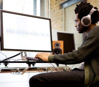 Junger Mann hört im Musikstudio mit seinen Over-Ear-Headphones