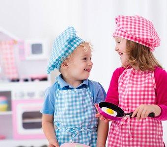 Geschwister üben ihre Fähigkeiten in einer Spielküche