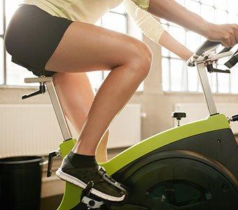 Seitliche Aufnahme einer Frau, welche auf einem Fahrrad-Ergometer trainiert.