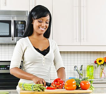 Lächelnde Frau hört Radiomusik beim Gemüseschneiden