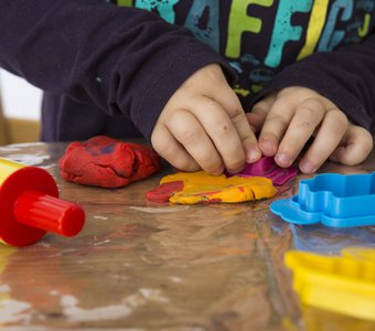 Nahaufnahme von Kinderhänden, die mit Knete spielen