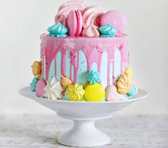 Türkise Torte mit verlaufener rosa Glasur verziert mit farbigen Maccaron, Zuckerhäubchen und Baiser