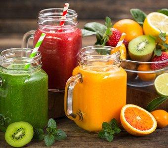 Drei verschiedene Smoothies mit einer Schale Obst und Gemüse
