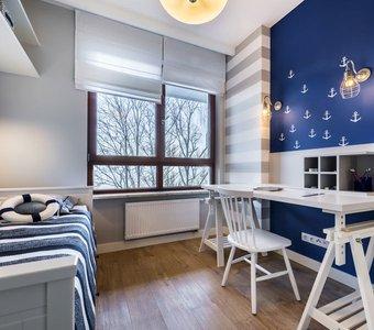 Blau-Weiß gestrichenes Zimmer mit Anker an der Wand uns Rettungsring als Deko