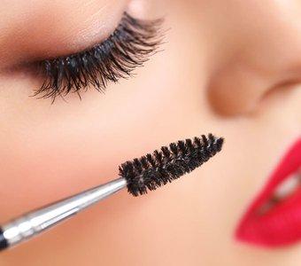 Nahaufnahme von dem Gesicht einer jungen Frau mit einer Wimpernbürste im Bild