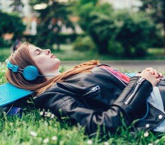 Teenagerin liegt im Park auf ihrem Skateboard und hört Musik