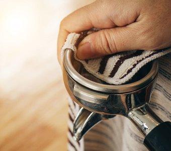 Bestandteil einer Kaffeemaschine wird mit einem Lappen gesäubert