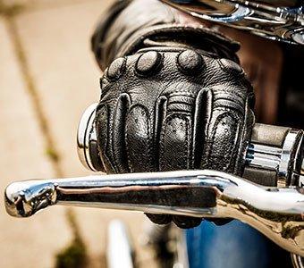 Ein lederner Motorradhandschuh am Lenker