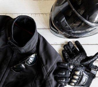 Schwarze Motorradschutzkleidung mit Helm, Handschuhen und Zündschlüssel