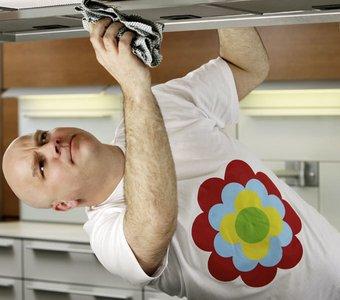 Mann reinigt seine Dunstabzugshaube von außen mit einem Lappen