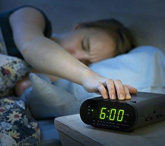 Frau im Bett greift nach Radiowecker