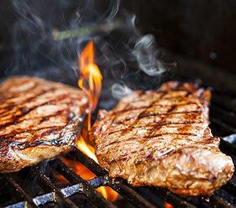 Nahaufnahme von zwei Stücken Fleisch auf einem Grill.