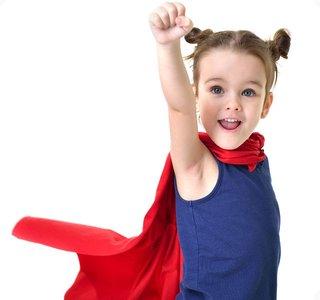 Mädchen mit Cape in Superman-Pose