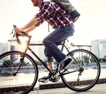 Mann mit Fahrrad und Rucksack in der Stadt unterwegs