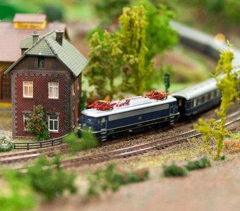 Modelleisenbahn auf mit Bäumen und Gebäuden gestalteter Eisenbahnplatte