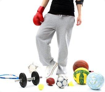 Mann in Trainingskleidung ist von unterschiedlichen Bällen und Trainingsgeräten umgeben