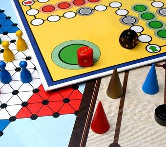 Verschiedene Brettspiele liegen übereinander mit Hüttchen und Würfeln