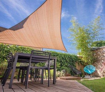 Sonnensegel schützt die Sitzgarnitur eines Gartens vor der Sonne