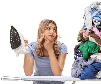 Blonde Frau schaut nachdenklich auf einen Wäscheberg und hält ein Bügeleisen in der Hand
