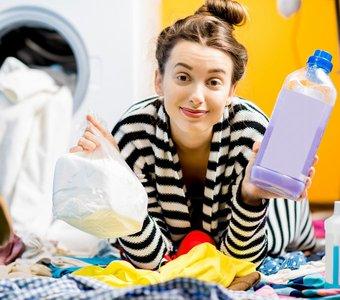 Junge Frau liegt zwischen ihrer Wäsche und hält Flüssig- und Pulverwaschmittel in der Hand