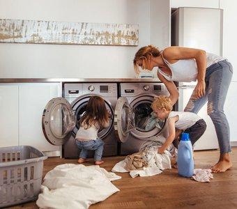 Mutter mit ihren Kindern beim Beladen des in die Küchenzeile integrierten Trockners