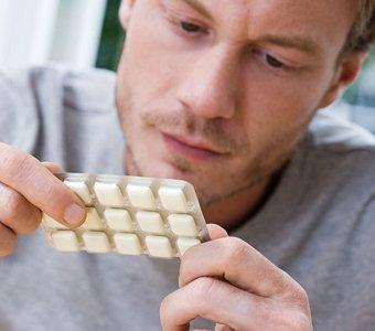 Junger Mann mit einer Packung Nikotinkaugummis