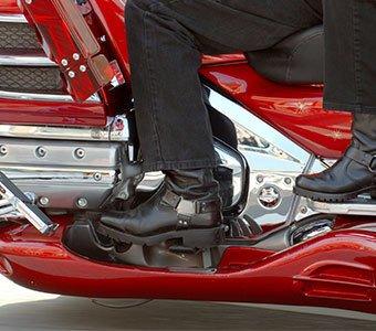 Aufnahme der Beine zweier Personen, welche auf einem Motorrad sitzen.