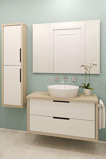 Aufnahme einer modernen Badezimmergarnitur mit Hängeschränken und einem Spiegel.