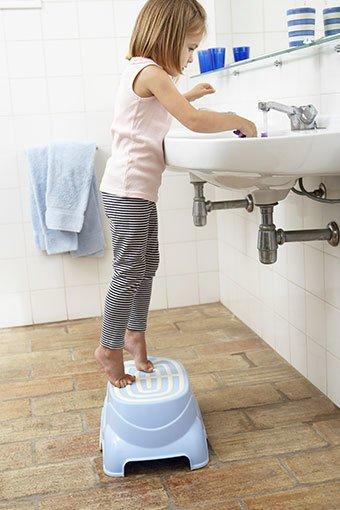 Aufnahme eines Kindes vor einem Waschbecken auf einem Badhocker.