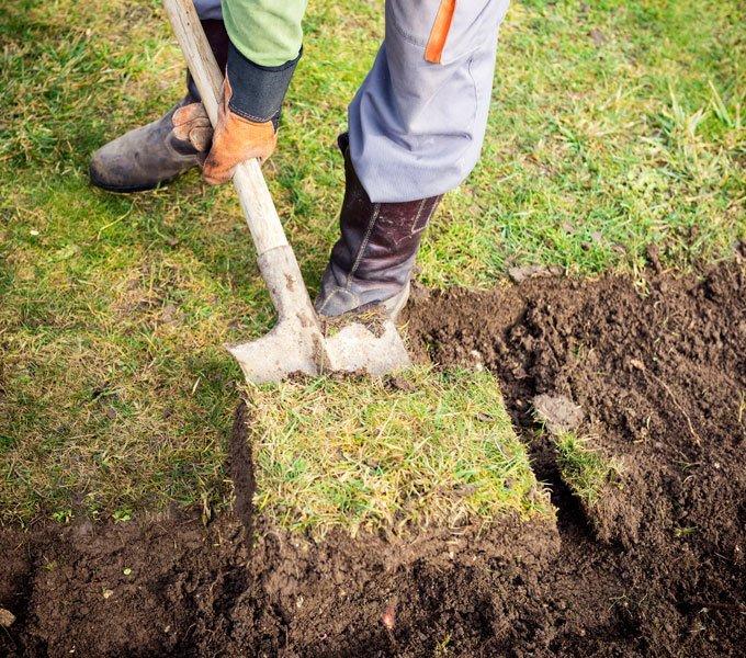 Eine Person gräbt mit einem Spaten den Boden um