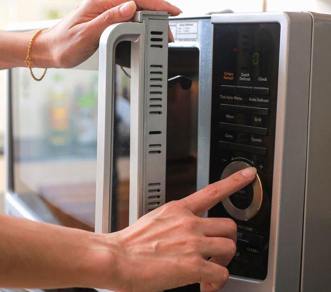 Frauenhand, die Einstellungen an einer Mikrowelle vornimmt