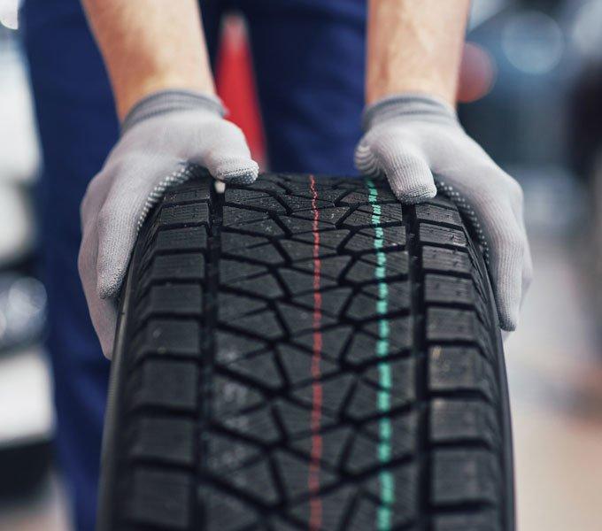 Ein neuer Reifen wird von einem KFZ-Mechaniker zur Werkstatt geschoben