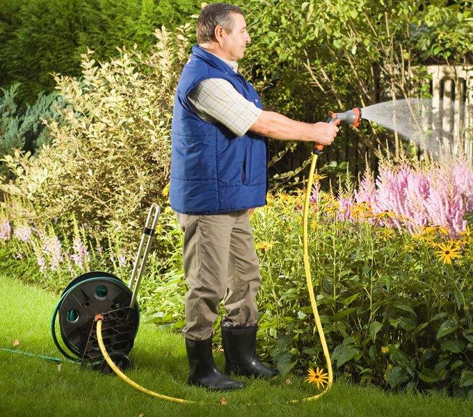 Mann, der mit einem auf einem Schlauchwagen aufgerollten Gartenschlauch Gartenpflanzen bewässert
