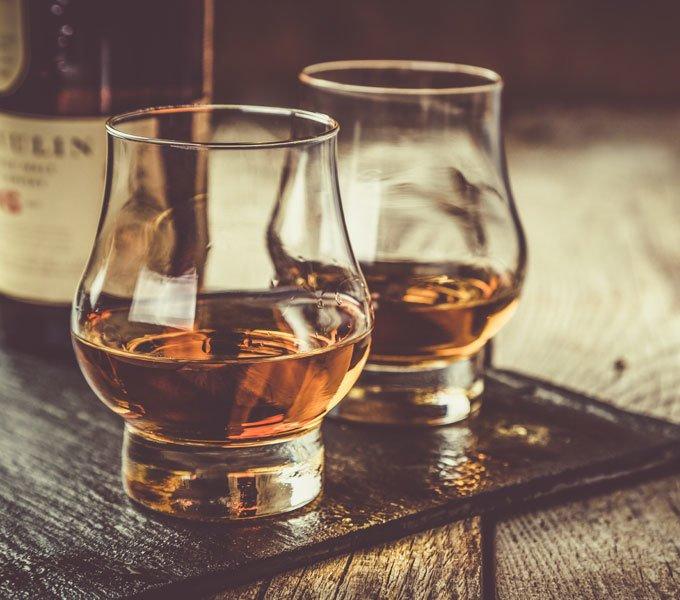 Zwei Gläser Whisky stehen auf einem Tisch