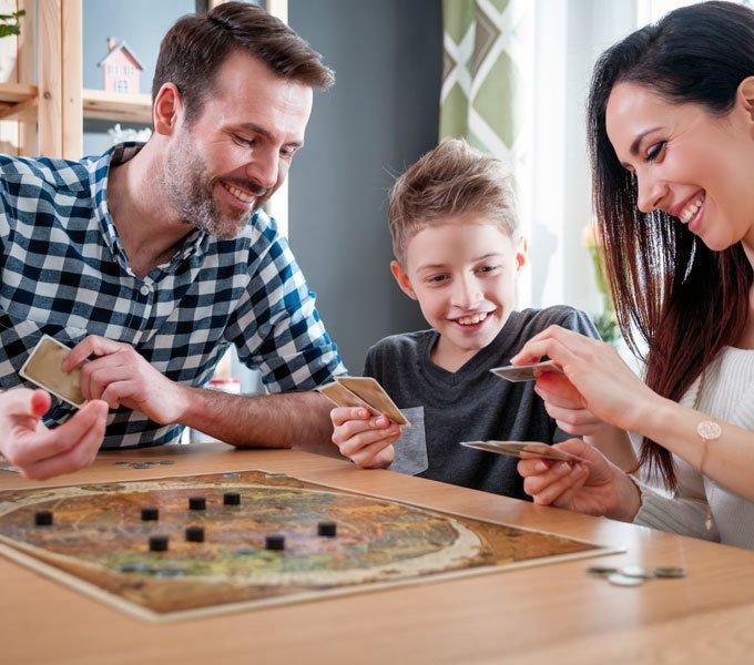 Junge spielt ein Brettspiel mit den Eltern