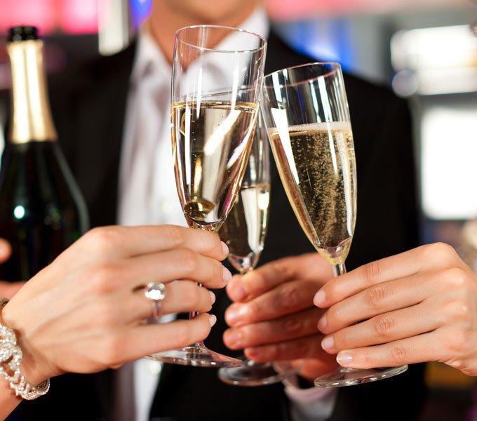 Drei mit Champagner gefüllte Sektgläser werden angestoßen