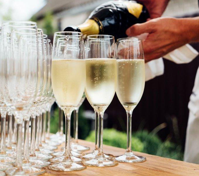 Mehrere Sektgläser werden vom einem Kellner mit Champagner aufgefüllt