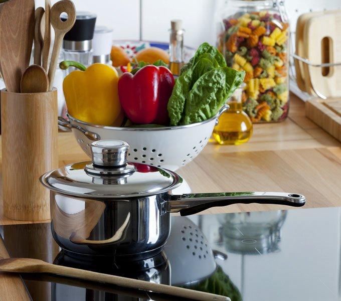 Topf auf einem Kochfeld, Behälter mit Kochwerkzeugen und ein Sieb mit frischem Gemüse