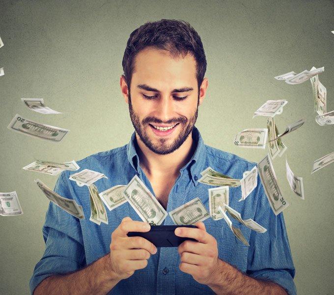 Mann schaut auf sein Smartphone. An den Seiten des Smartphones entweichen Geldnoten