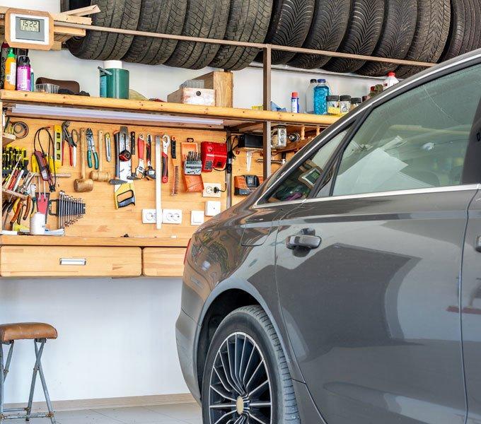 Hinter einem eingeparkten PKW hängt das Werkzeug an der Wand