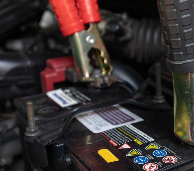 Nahaufnahme zweier an einer Autobatterie befestigter Krokodilklemmen