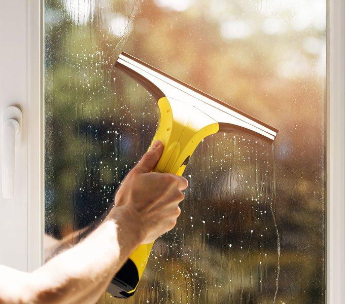 Ein junger Mann putzt seine Fenster mit einem modernen Fenstersauger