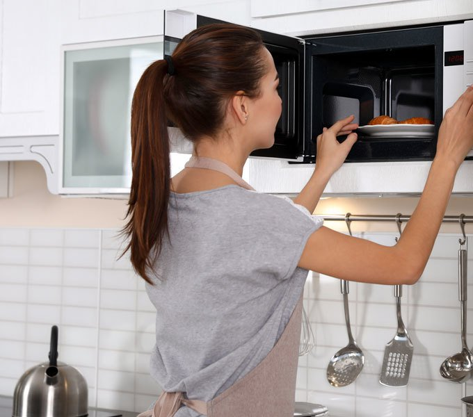 Frau, die einen Teller aus einer Einbau-Mikrowelle entnimmt