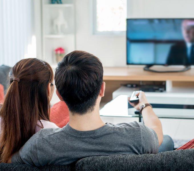 Zwei Personen schauen eine Serie auf dem Fernseher