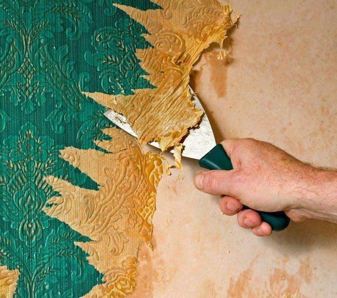 Eine grüne Tapete wird mit einem Spachtel von der Wand gekratzt