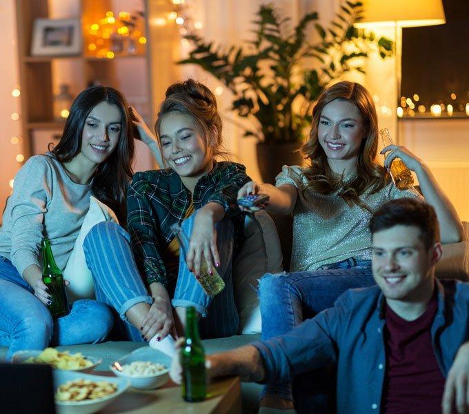 Junge Leute sitzen auf der Couch, gucken Fernsehen und Essen zusammen