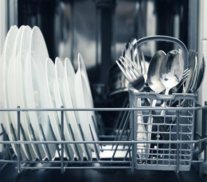 Sauberes Besteck steht in einem Geschirrspüler zur Entnahme bereit